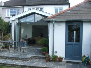 Extension sits behind the garage, creating a sheltered living space.
